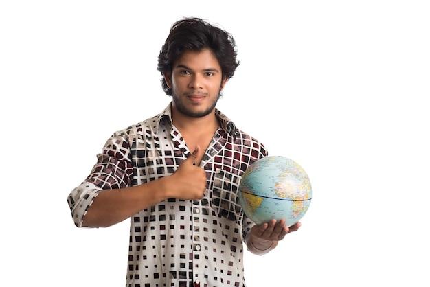 Młody człowiek z kuli ziemskiej na białym tle.