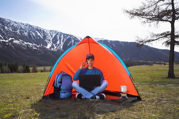Młody człowiek z laptopa siedzi w namiocie na tle gór i wzgórz ałtaju i rozmawia przez telefon komórkowy. pojęcie pracy zdalnej lub stylu życia freelancera