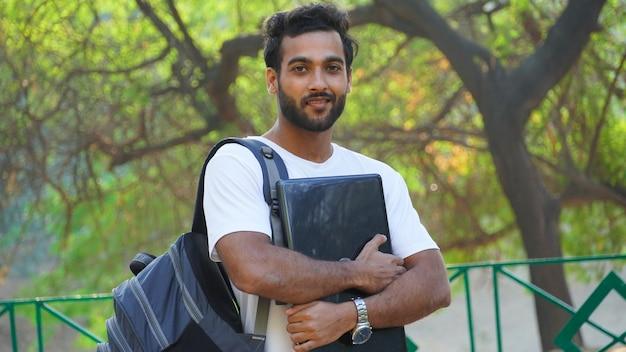 Młody człowiek z laptopem i torbą na kampusie uczelni