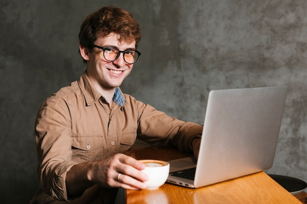 Młody człowiek z laptopem ono uśmiecha się