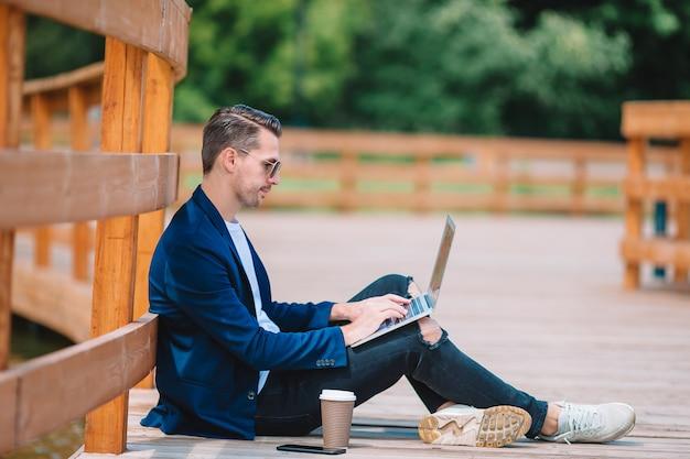 Młody człowiek z laptopem pracuje outdoors w parku