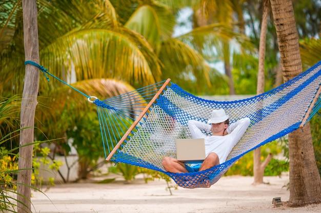 Młody człowiek z laptopem przy hamakiem na tropikalnym wakacje