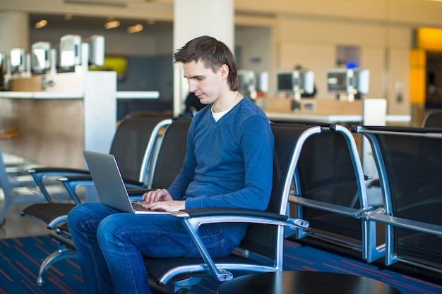 Młody człowiek z laptopem przy lotniskiem podczas gdy czekający jego lot