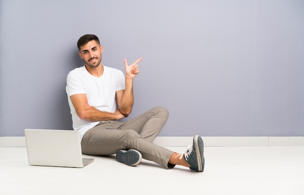 Młody człowiek z laptopem siedzi jeden podłogowy palec wskazujący z boku