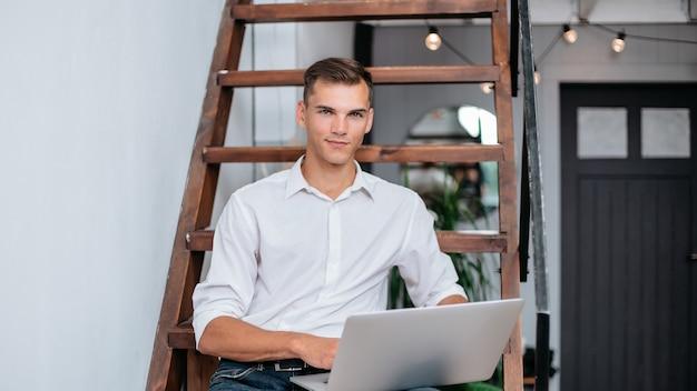 Młody człowiek z laptopem siedzi na schodach w swoim apartmant