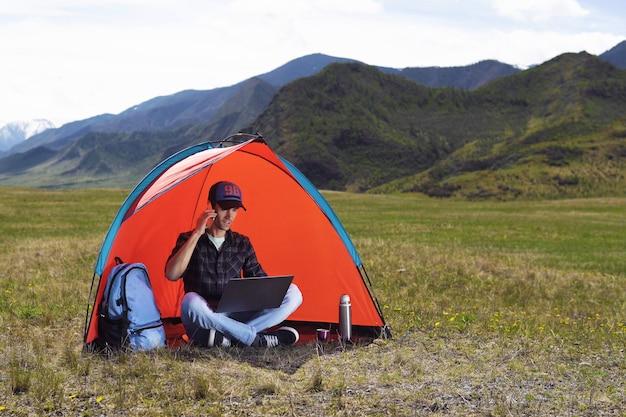 Młody człowiek z laptopem siedzi w namiocie przeciw górom i wzgórzom ałtaj i opowiada na telefonie komórkowym.