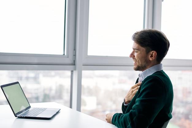 Młody człowiek z laptopem w garniturze, pracujący w biurze iw domu przy oknie, przeprowadzający wywiad online