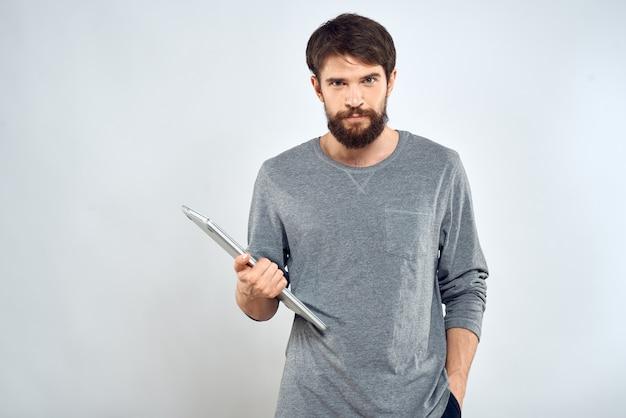 Młody człowiek z laptopem w rękach na białym tle