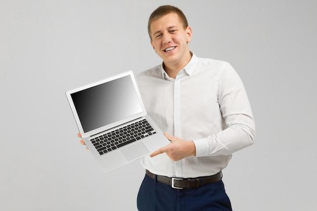 Młody człowiek z laptopem z pustym ekranem w jego rękach odizolowywa na lekkim tle