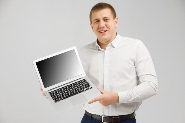 Młody człowiek z laptopem z pustym ekranem w jego rękach