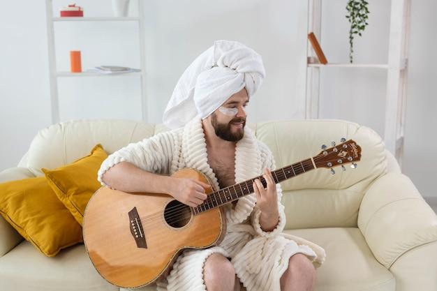 Młody człowiek z łatami pod oczami gra na gitarze w domu koncepcja kosmetologii dla mężczyzn i