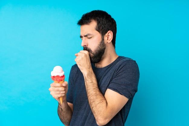 Młody człowiek z lodami kornetowymi na izolowanej niebieskiej ścianie cierpi na kaszel i źle się czuje