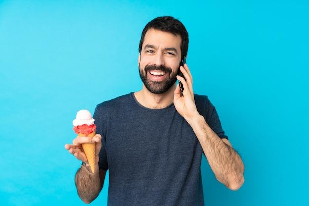 Młody człowiek z lodami kornetowymi prowadzący z kimś rozmowę z telefonem komórkowym