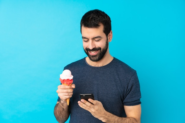 Młody człowiek z lodami lody na pojedyncze niebieskie ściany, wysyłając wiadomość z telefonu komórkowego