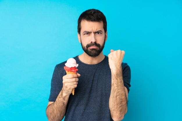 Młody człowiek z lodów kornaku na pojedyncze niebieskie ściany z gniewnym gestem