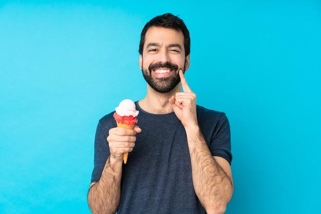 Młody człowiek z lodów kornet na izolowanych niebieską ścianą, uśmiechając się z wyrażeniem szczęśliwy i przyjemny