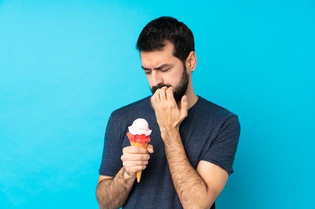 Młody człowiek z lodów kornet na pojedyncze niebieskie ściany, mając wątpliwości