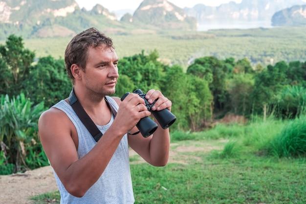 Młody człowiek z lornetką w ręku obserwując dziką przyrodę w tropikach.