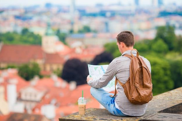 Młody człowiek z mapą miasta i plecakiem. kaukaski turysta patrząc na mapę europejskiego miasta z pięknym widokiem na atrakcje.