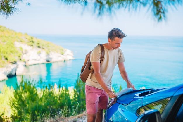 Młody człowiek z mapą podróżuje samochodem na wakacje