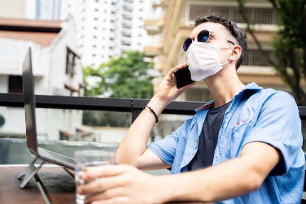 Młody człowiek z maską i okularami przeciwsłonecznymi pracujący zdalnie z laptopem i rozmawiający z telefonem komórkowym na zewnątrz