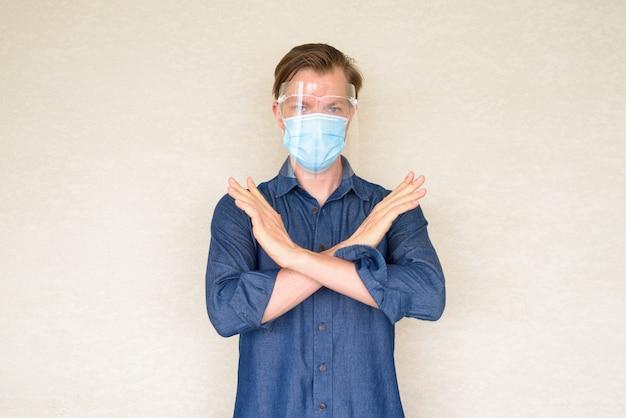 Młody człowiek z maską i osłoną twarzy pokazuje gest stopu na betonowej ścianie