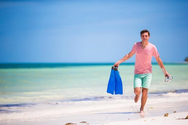 Młody człowiek z maską i płetwami. wakacje na tropikalnej plaży.