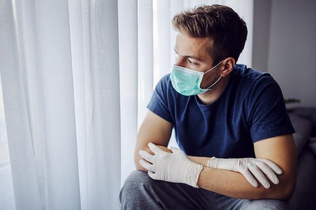 Młody człowiek z maską i rękawiczkami, patrząc przez okno. zostań w domu, bądź odpowiedzialny. sam w domu.