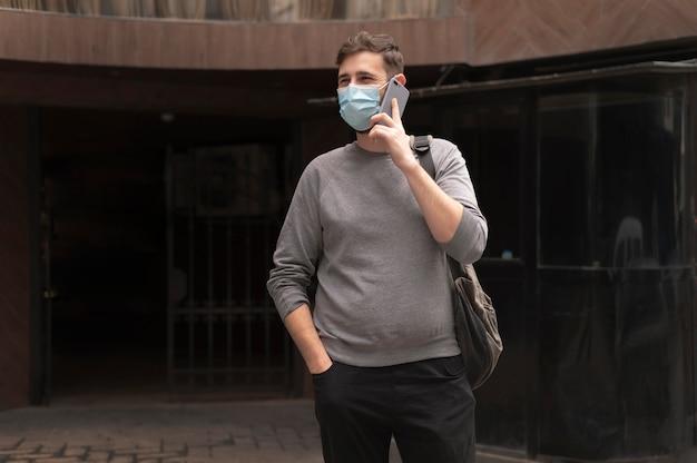 Młody człowiek z maską medyczną rozmawia przez telefon na zewnątrz