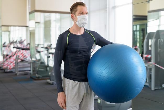 Młody człowiek z maską myśli, trzymając piłkę do ćwiczeń na siłowni podczas koronawirusa covid-19
