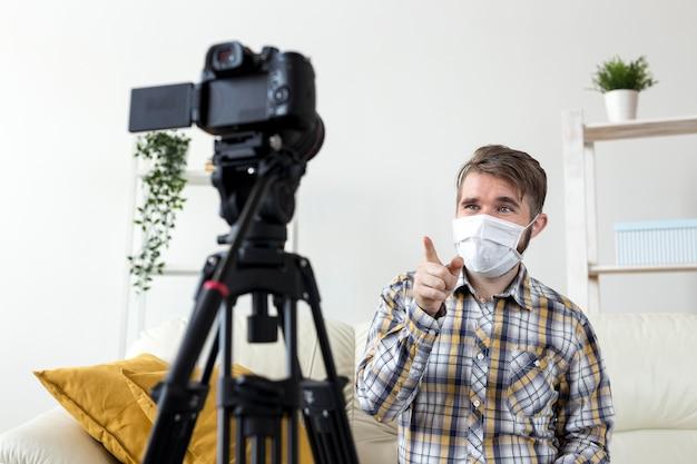 Młody człowiek z maską na twarz nagrywanie wideo w domu