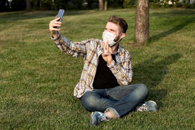 Młody człowiek z maską na zewnątrz, biorąc selfie