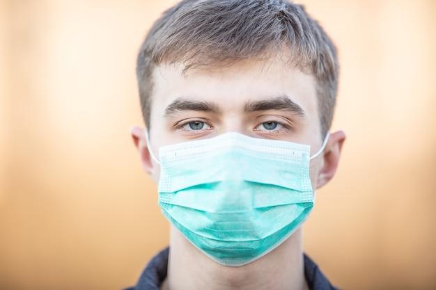 Młody człowiek z maską ochronną na twarzy. ochrona przed kurzem wirusowym lub smogiem. koncepcja koronawirusa covid-19.