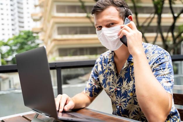 Młody człowiek z maską ochronną na twarzy pracuje zdalnie z laptopem i rozmawia z telefonem komórkowym