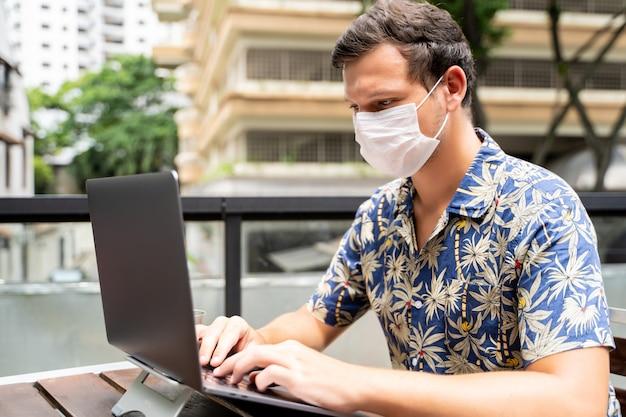 Młody człowiek z maską ochronną na twarzy pracuje zdalnie ze swoim laptopem