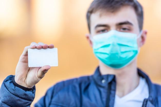 Młody człowiek z maską ochronną na twarzy trzymając pustą białą kartę... ochrona przed wirusem, kurzem lub smogiem. koncepcja koronawirusa covid-19.