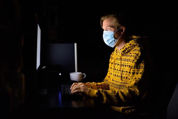 Młody człowiek z maską pracuje w domu późno w nocy w ciemności