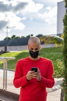 Młody człowiek z maską, sprawdzanie swojego telefonu komórkowego i mówienie w parku