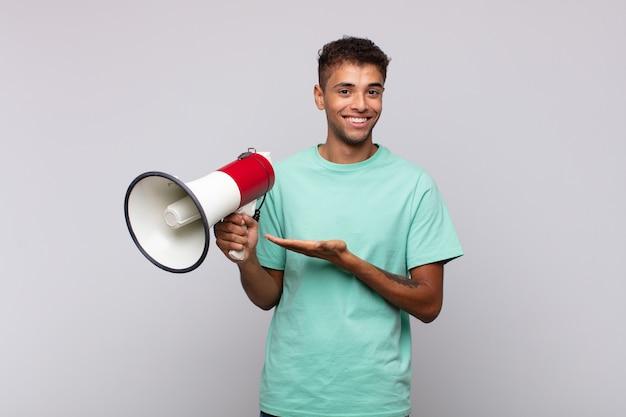 Młody człowiek z megafonem uśmiecha się radośnie, czuje się szczęśliwy i pokazuje koncepcję w przestrzeni kopii z dłonią