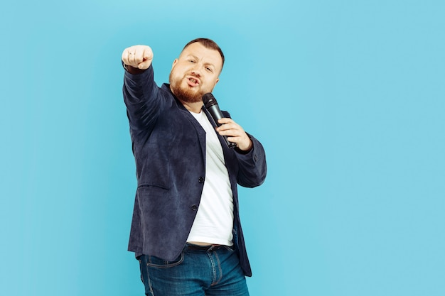 Młody człowiek z mikrofonem na błękit ścianie, wiodący pojęcie