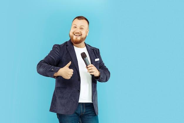 Młody człowiek z mikrofonem na błękitnym tle, wiodący pojęcie