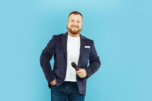 Młody człowiek z mikrofonem na niebieskiej przestrzeni, wiodąca koncepcja