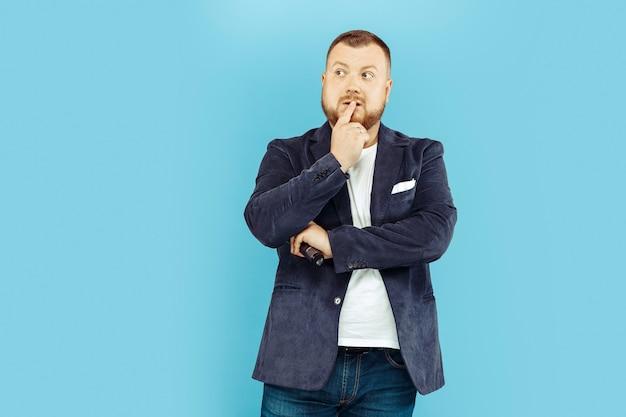 Młody człowiek z mikrofonem na niebieskiej ścianie
