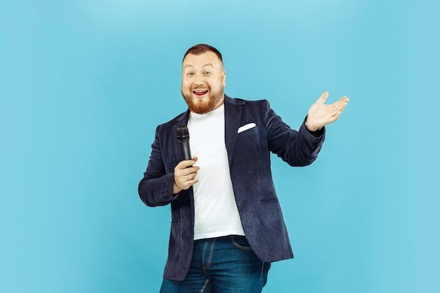 Młody człowiek z mikrofonem na niebieskim studio, wiodąca koncepcja