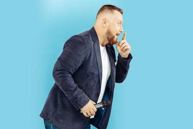 Młody człowiek z mikrofonem na niebiesko, wiodąca koncepcja