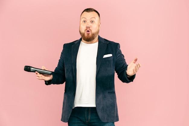 Młody człowiek z mikrofonem na różowej przestrzeni, prowadząc z mikrofonem