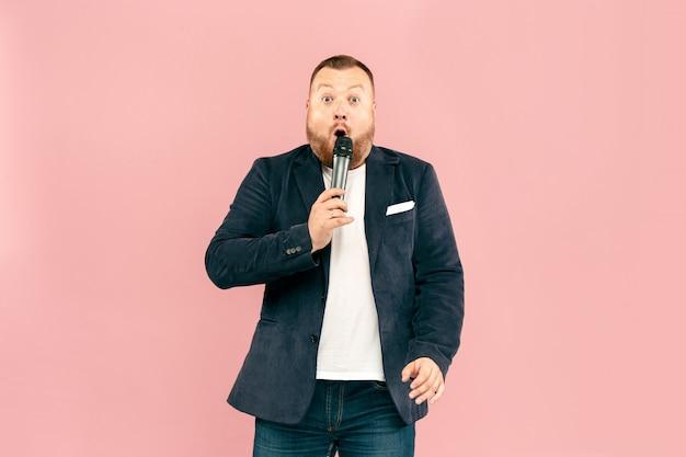 Młody człowiek z mikrofonem na różowo, prowadzący z mikrofonem