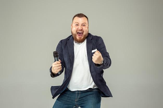 Młody człowiek z mikrofonem na szarej ścianie