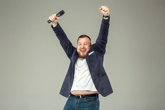 Młody człowiek z mikrofonem na szaro, prowadzący z mikrofonem