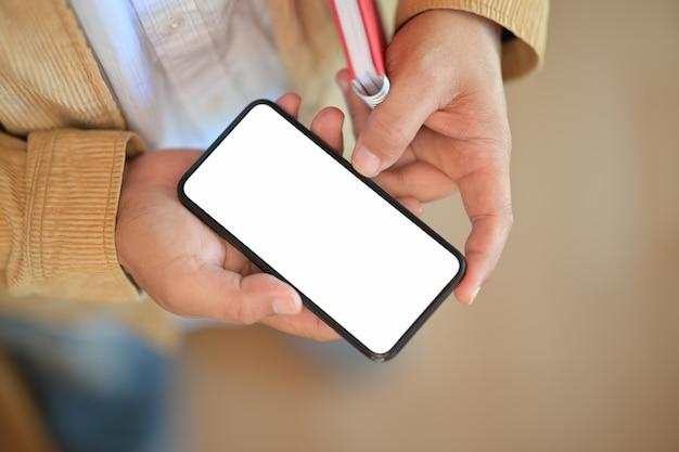 Młody człowiek z mockup pustego ekranu mobilnym mądrze telefonem